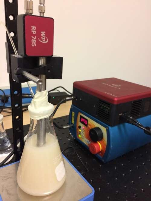 Fermentation Setup (front) on magnetic stirrer (bottom) with probe (top) and spectrometer and laser (back).