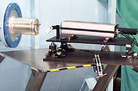 A dynamic interferometer measures a test sample in a vacuum chamber through a view port