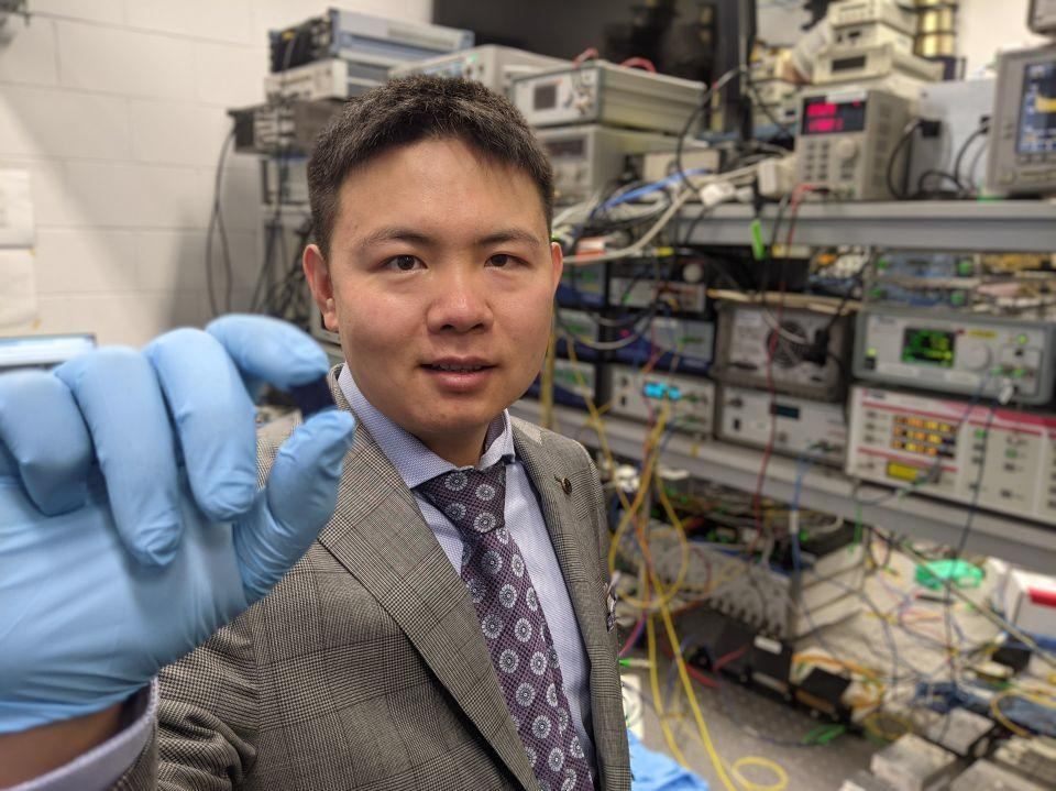 Dr Xingyuan (Mike) Xu with the integrated optical microcomb chip, which forms the core part of the optical neuromorphic processor.