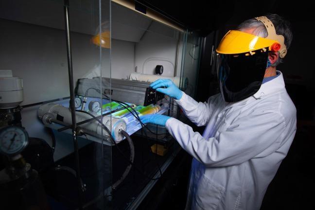 Jacek Koziel adjusts infrared lamps and sensors in a Sukup Hall laboratory.
